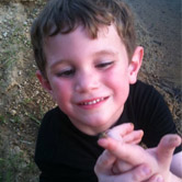 A child looking at an insect on his finger.