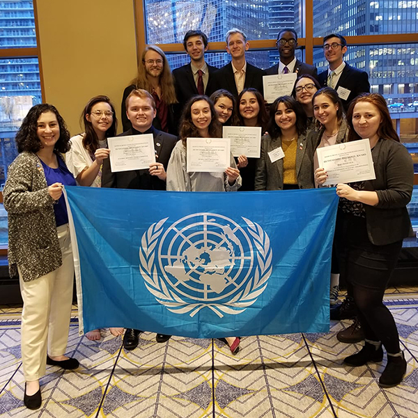 Group of students pose for photo with their awards and a blue Model UN flag